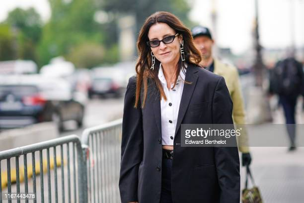 A guest wears Chanel sunglasses Chanel rhinestone earrings a Chanel white crop shirt outside the Chanel Cruise Collection 2020 At Grand Palais on May...
