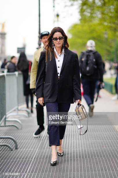 A guest wears Chanel sunglasses Chanel rhinestone earrings a Chanel white crop shirt a black jacket navy blue jeans two tons black shoes a rattan...