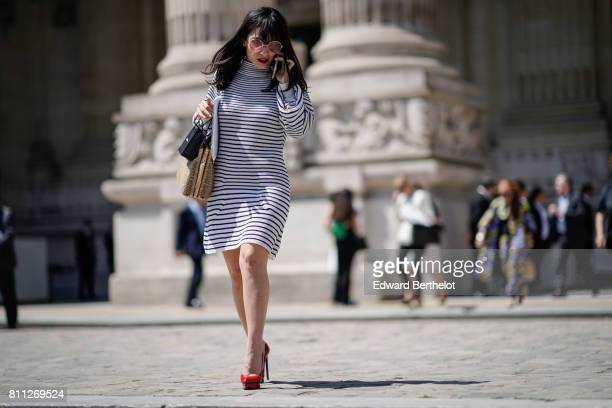 A guest wears circular clear sunglasses a striped dress red heels shoes outside the Chanel show during Paris Fashion Week Haute Couture Fall/Winter...