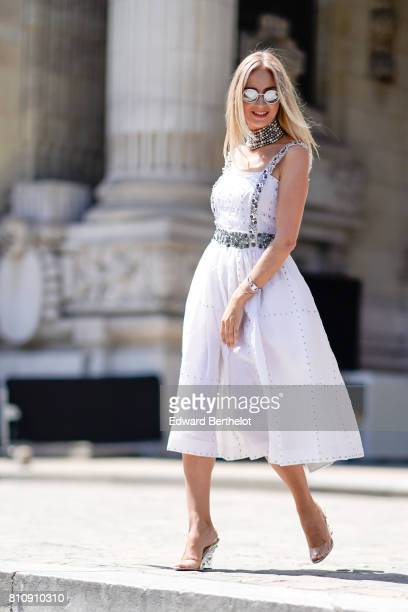 A guest wears circular silver sunglasses a white dress heels shoes outside the Chanel show during Paris Fashion Week Haute Couture Fall/Winter...