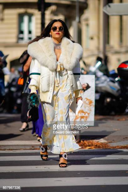 A guest wears circular sunglasses a fur coat a dress shoes outside Miu Miu during Paris Fashion Week Womenswear Spring/Summer 2018 on October 3 2017...