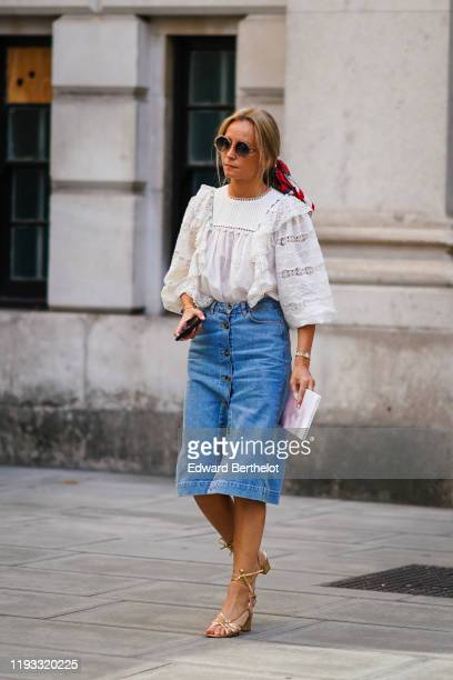 Guest wears circular sunglasses, a white mesh ruffled lace top, a blue denim skirt, golden shoes, during London Fashion Week September 2019 on...