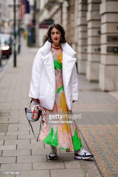 A guest wears colorful earrings a white puffer jacket a peachcolor hineck dress with green and yellow spots and black polka dots a blue and grey...
