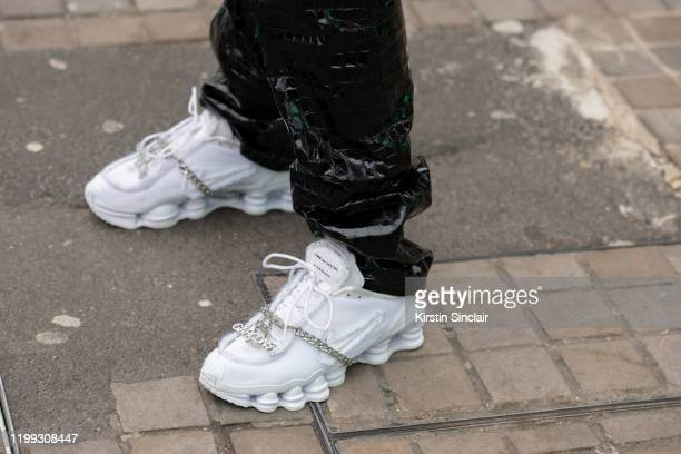 A guest wears Comme Des Garcons Nike Shox trainers with pvc trousers during London Fashion Week Men's January 2020 on January 05 2020 in London...