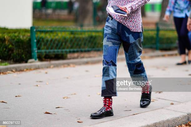 A guest wears denim shades of blue patchwork pants red print socks black moccasins outside Lanvin during Paris Fashion Week Womenswear Spring/Summer...