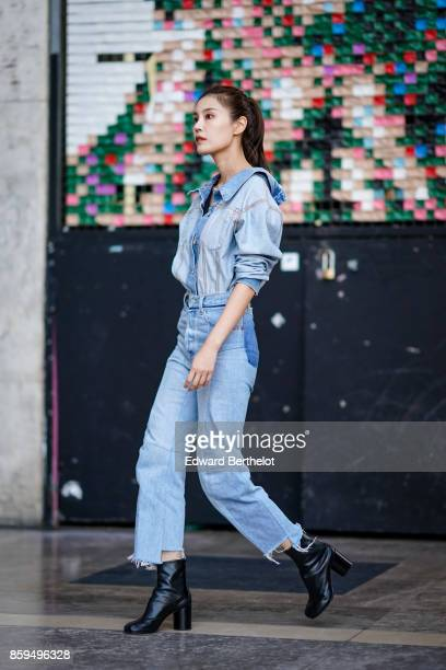 A guest wears denim shirt denim pants and black boots outside the Rochas show during Paris Fashion Week Womenswear Spring/Summer 2018 on September 27...