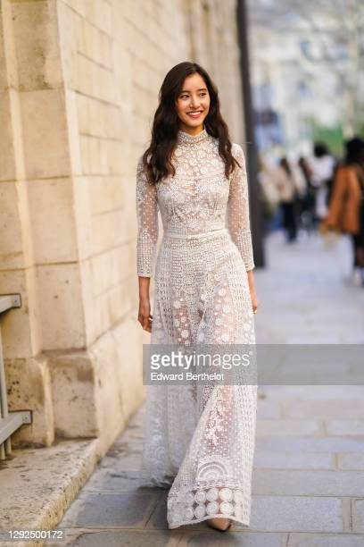 Guest wears Dior earrings, a high neck white lace see-through mesh full-length dress with floral embroidery, outside Dior, during Paris Fashion Week...