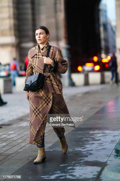 A guest wears earrings a beige and black plaid wool wrapover coat a black bag sandcolor suede ankleboots outside Louis Vuitton during Paris Fashion...