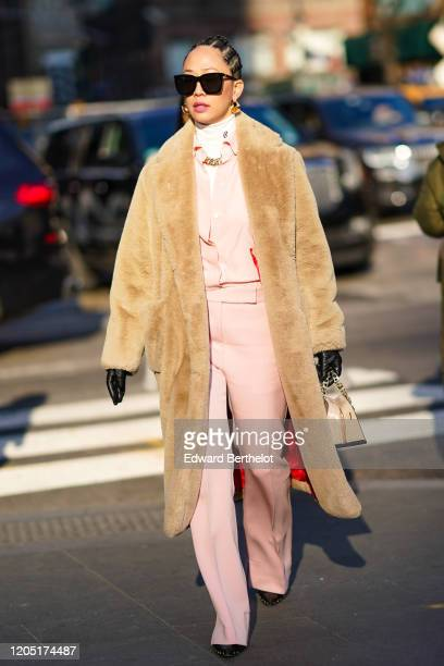 A guest wears earrings a beige fluffy long coat with red silky inner lining a white turtleneck a metallic necklace a pink jacket pale pink flared...