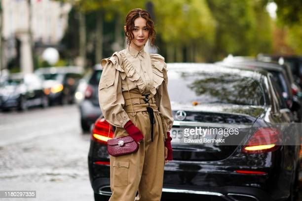 A guest wears earrings a beige long sleeves frilly shirt red mittens a shiny red crocodile pattern bag sand color baggy pants a sand color lace up...