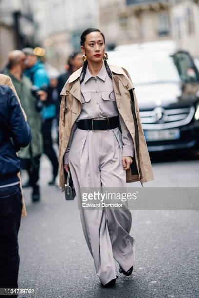 A guest wears earrings a beige shirt a large black belt beige baggy pants a camel trench coat a shiny silver handbag black shoes outside Thom Browne...