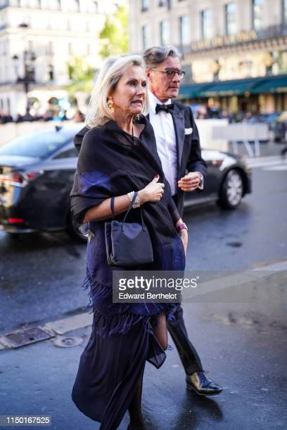 A guest wears earrings a black and navy blue fringed scarf a black bag a pearl bracelet a black halter long dress black pumps outside the Opera...