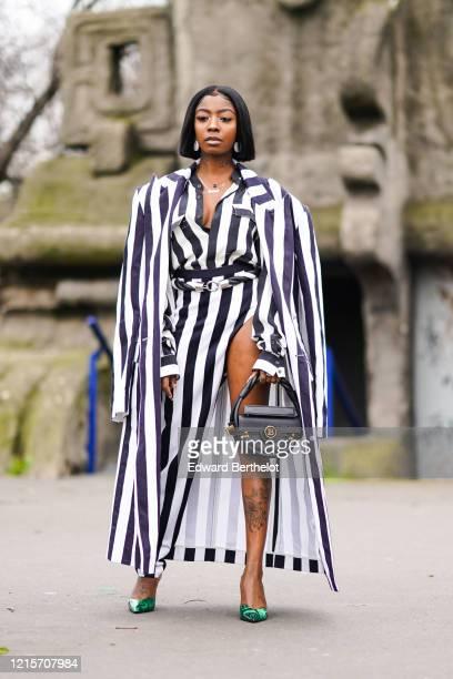 Guest wears earrings, a black and white striped asymmetric open leg dress, a belt, a long coat, green pointy shoes, a black leather Balmain circular...