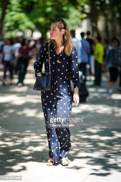 A guest wears earrings a black bag a navy blue with yellow polka dots jumpsuit shiny golden strappy sandals outside Berluti during Paris Fashion Week...