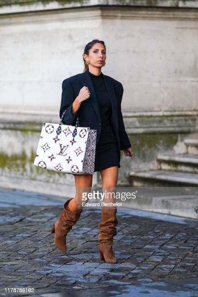 A guest wears earrings a black blazer jacket a Vuitton monogram large bag a black top a skirt brown suede high boots outside Louis Vuitton during...