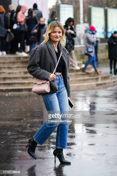 Guest wears earrings, a black crop top, a grey and black houndstooth jacket, ripped blue jeans, black pointy heeled boots, a pale pink bag, outside...
