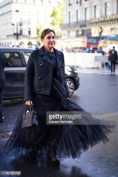 A guest wears earrings a black doublebreasted jacket a black ruffled and gathered flowing muslin long dress a black embroidered handbag black pumps...