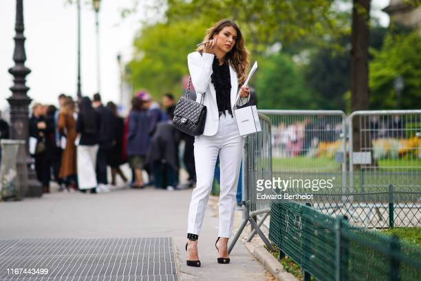 A guest wears earrings a black frilly top a black Chanel bag a white jacket white pants ankle strap with buckles black sandals outside the Chanel...
