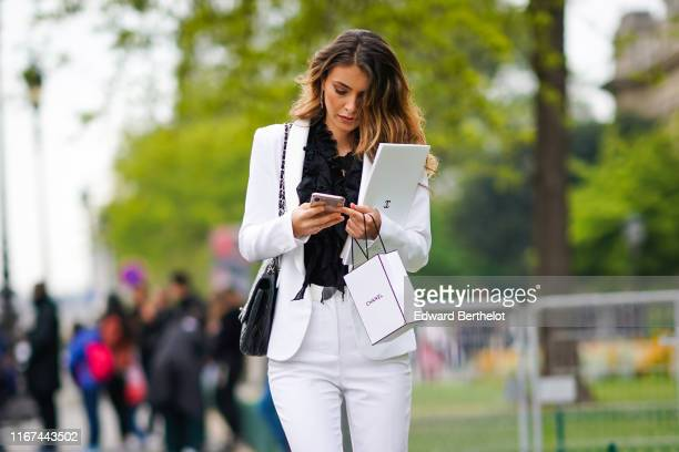 A guest wears earrings a black frilly top a black Chanel bag a white jacket white pants outside the Chanel Cruise Collection 2020 At Grand Palais on...