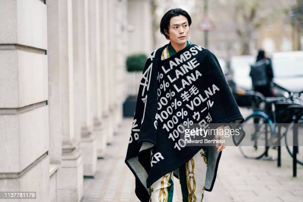 A guest wears earrings a black poncho with white inscriptions white green and golden color scarf design pants during London Fashion Week February...