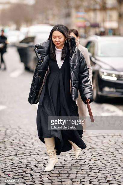 Guest wears earrings, a black puffer jacket, a white turtleneck, a black low-cut pleated dress, white pointy high-heeled boots, outside Altuzarra,...
