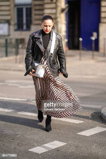 A guest wears earrings a black studded leather jacket a black top a striped dress a white bag during Paris Fashion Week Womenswear Fall/Winter...