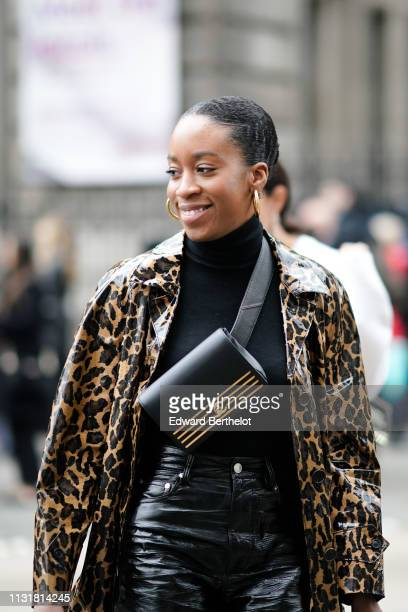 A guest wears earrings a black turtleneck a shiny leopard print vinyl trench coat a black Chanel bag during London Fashion Week February 2019 on...
