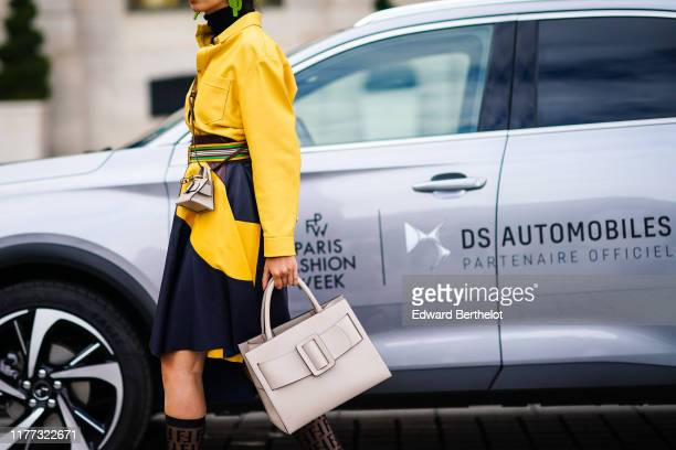 A guest wears earrings a black turtleneck a yellow leather shirt a colorful belt a brown black and yellow leather asymmetric and patched skirt a tiny...