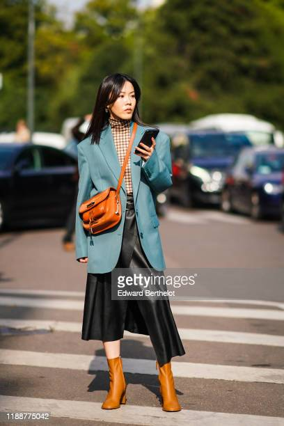 Guest wears earrings, a brown checkered hi-neck top, an ocean-blue oversized jacket, a tan-color crossbody bag, a black leather asymmetric wrap-over...