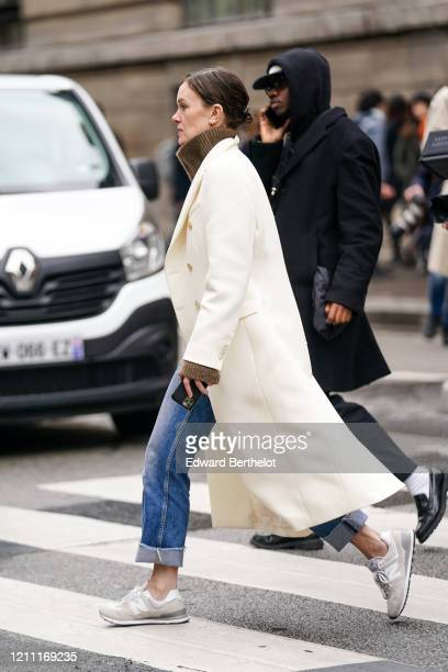 Guest wears earrings, a brown cowl collar sweater, a white coat, blue crop jeans with rolled-up hem, beige New Balance sneakers, outside Giambattista...