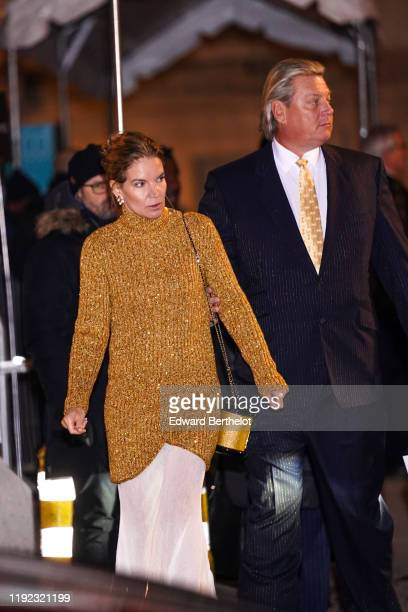 Guest wears earrings, a brown wool turtleneck long pullover, a golden glittering cylinder shaped bag, after the Chanel Metiers D'Art 2019-2020 at the...