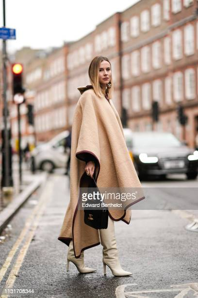A guest wears earrings a brownhemmed large camel cape a black Céline bag beige pointy boots during London Fashion Week February 2019 on February 18...