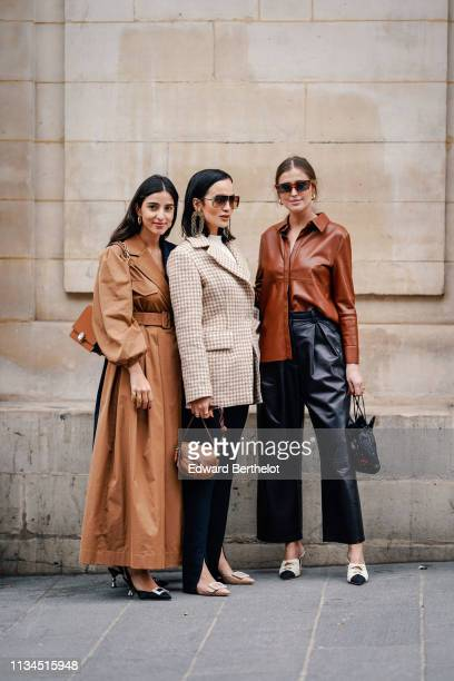 A guest wears earrings a camel long coat a Miu Miu brown leather bag black slingback pumps with fantasy heels and bejewelled buckles a guest wears...