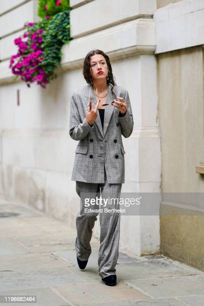 A guest wears earrings a checked blazer gray jacket flare pants black shoes a ring during London Fashion Week September 2019 on September 16 2019 in...