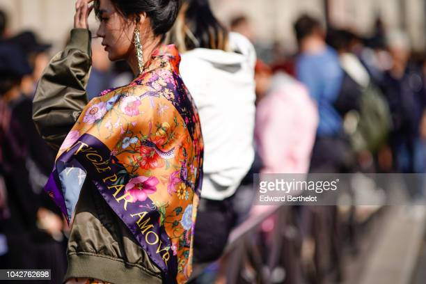 A guest wears earrings a colored silk floral print scarf outside Balmain during Paris Fashion Week Womenswear Spring/Summer 2019 on September 28 2018...