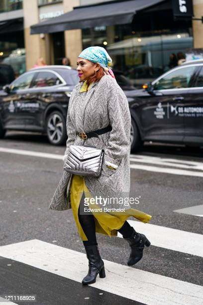 Guest wears earrings, a colorful headscarf, a grey coat with a black Balenciaga belt, a metallic-tone Yves Saint Laurent quilted bag, a yellow...
