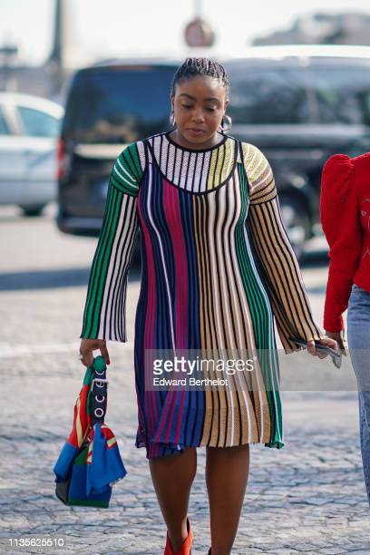 A guest wears earrings a colorfully striped top a colorfully striped strapped dress a colorful scarf a green bag outside Unravel Project during Paris...