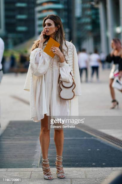 Guest wears earrings, a cream-color pleated embroidered mini dress with puff sleeves, a cream-color embroidered coat, a cream-color handbag decorated...