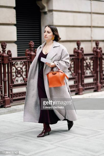 A guest wears earrings a deep burgundy lowcut dress a light grey Prince of Wales check oversize coat an orange Danse Lente handbag brown and burgundy...
