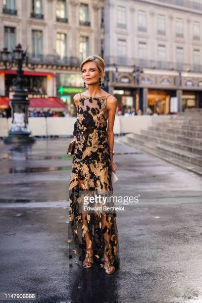 Guest wears earrings, a golden and black lace mesh dress with embroidery, outside the Opera Garnier 350th Anniversary Gala in Paris on May 08, 2019...