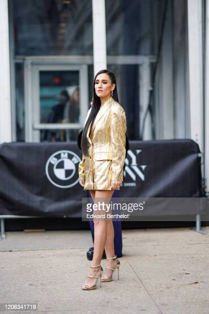 A guest wears earrings a golden shiny oversized glittering oversized blazer jacket/dress high heeled shoes during New York Fashion Week Fall Winter...