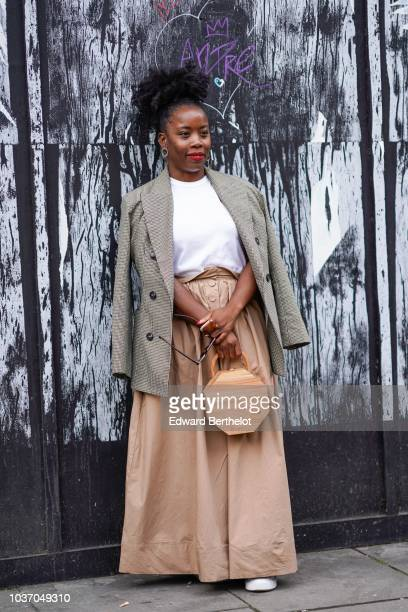 A guest wears earrings a gray blazer jacket a wite tshirt a beige skirt a wooden bag during London Fashion Week September 2018 on September 14 2018...