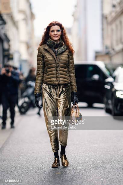 A guest wears earrings a green and yellow scarf a lustrous brown puffer jacket lustrous golden velvet pants a brown bag black gloves shiny bronze...