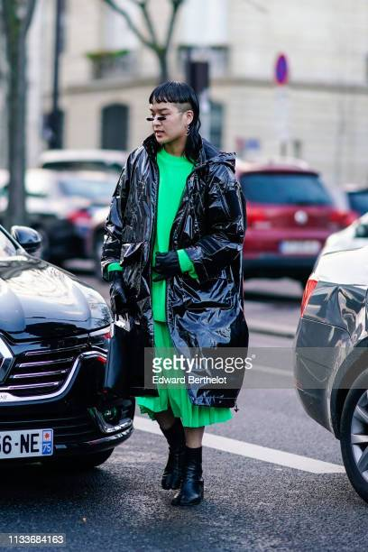 A guest wears earrings a green suit with a pleated skirt a shiny black vinyl raincoat black divided end ankle boots outside Shiatzy Chen during Paris...