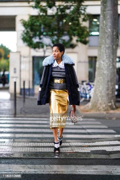A guest wears earrings a grey and black jacquard sweater with a white lace collar a fur collar navy blue suede jacket with wool knit sleeves a shiny...