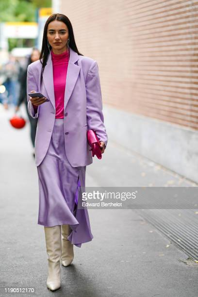 A guest wears earrings a hot pink hineck top a hot pink bag a mauve jacket a lustrous mauve skirt creamcolor pointy heeled boots outside the Fendi...