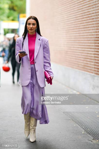 Guest wears earrings, a hot pink hi-neck top, a hot pink bag, a mauve jacket, a lustrous mauve skirt, cream-color pointy heeled boots, outside the...