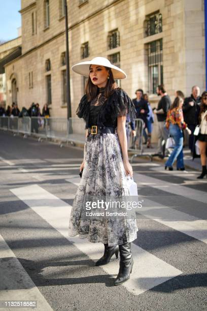 """Guest wears earrings, a large white hat, a black lace top, a black and white Toile de Jouy design flowing skirt, a black """"Diorquake"""" Dior belt, black..."""