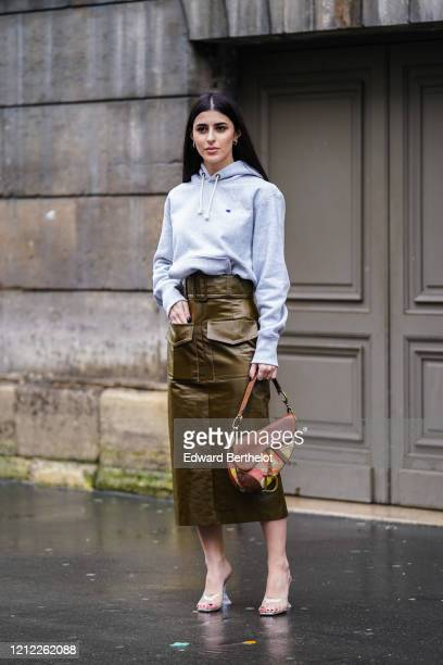 Guest wears earrings, a light grey hooded sweatshirt, a colorful Dior saddle bag with a brown flap, a bronze-tone leather skirt with pockets,...