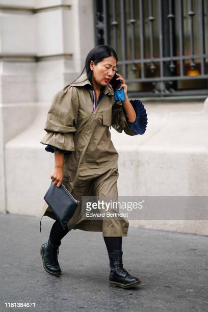 A guest wears earrings a light khaki wrapover trench coat with ruffled sleeves a black clutch black armystyle laceup boots outside Ralph Russo during...